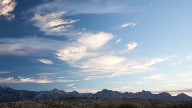 WS T/L View of clouds moving over land scap and passing mountains at sunsets / Tucson, Arizona, United States