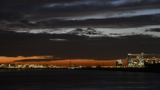 WS T/L View of clouds moving over river Scheldt and petrochemical industry in port of Antwerp at dusk / Antwerp, Antwerp, Belgium