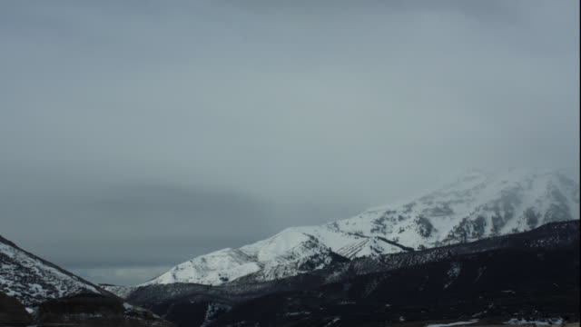 ws t/l view of clouds moving over snowy mountains / provo, utah, usa - provo stock videos & royalty-free footage