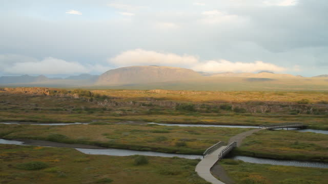 ws view of clouds rolling over mountain with grasslands and streams / porvaldseyri, sudhurland, iceland - wiese video stock e b–roll
