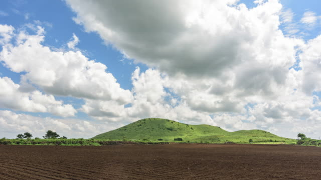 View of cloudscape over Yongnunioreum Hill (Cinder Cone; Popular travel destination) and Farming Field