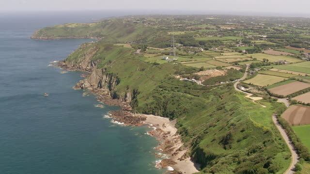ws aerial view of coastline and farm field / guernsey, channel isles - guernsey stock-videos und b-roll-filmmaterial