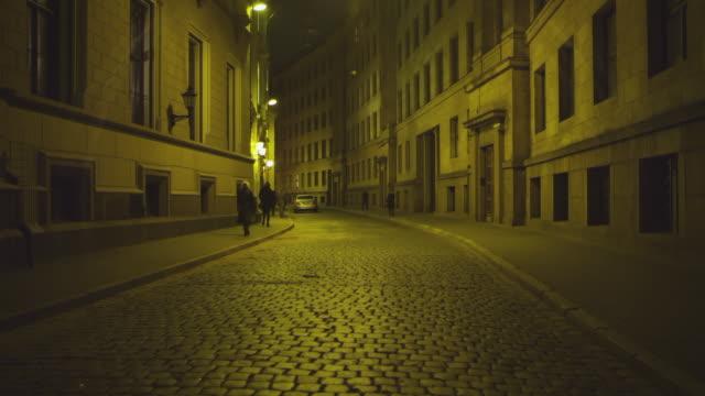 ws r/f view of cobblestone street with people at night / riga, latvia - dissolvenza in chiusura video stock e b–roll