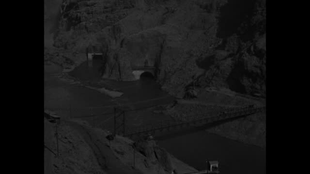 view of colorado river in canyon hoover dam construction site upstream in near distance portals of diversion tunnels in canyon wall in foreground /... - hoover staudamm stock-videos und b-roll-filmmaterial