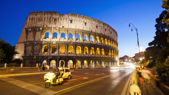 ws t/l view of colosseum at dusk with traffic / rome, lazio, italy  - colosseum rome stock videos and b-roll footage