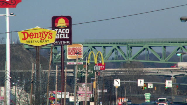 ws view of commercial street with many fast food signs and bridge in background - sign stock videos & royalty-free footage
