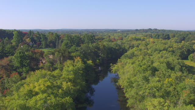 WS AERIAL POV View of Concord River surrounded by autumn tree / Concord, Massachusetts, United States