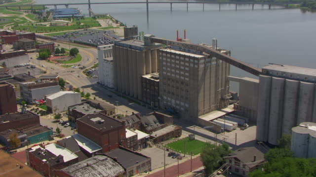 ws aerial pov view of congra flour mill with city, mississippi river in background / alton, illinois, united states - flour mill stock videos & royalty-free footage