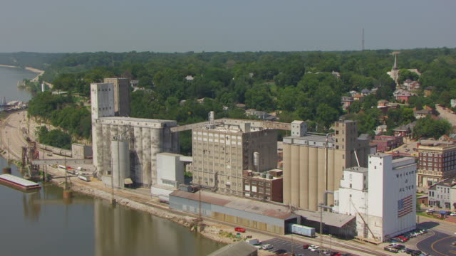 ws aerial pov view of congra flour mill with mississippi river in background / alton, illinois, united states - flour mill stock videos & royalty-free footage
