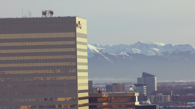ms aerial view of conoco phillips building with mountains in distance / anchorage, alaska, united states - anchorage alaska stock videos & royalty-free footage