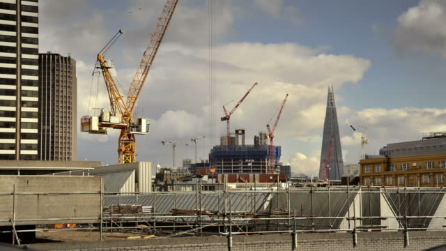 ws t/l view of construction cranes moving at number of locations in central with roof of national theatre and clouds in back side / london, greater london, united kingdom - continuity stock videos & royalty-free footage