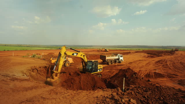 view of construction site, excavator loading earth into dump truck - construction vehicle stock videos & royalty-free footage