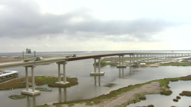 ws aerial view of construction trucks driving over leeville bridge section of highway la 1 over water / louisiana, united states - bayou lafourche stock-videos und b-roll-filmmaterial