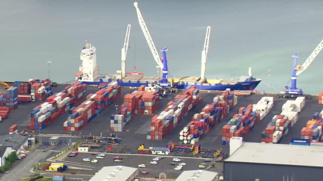 vídeos de stock, filmes e b-roll de ms aerial view of container yard with cargo ship / iceland - coluna de calcário marítimo