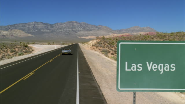ws pan view of convertible car on road with 'las vegas' 125 sign on road - segnaletica stradale video stock e b–roll