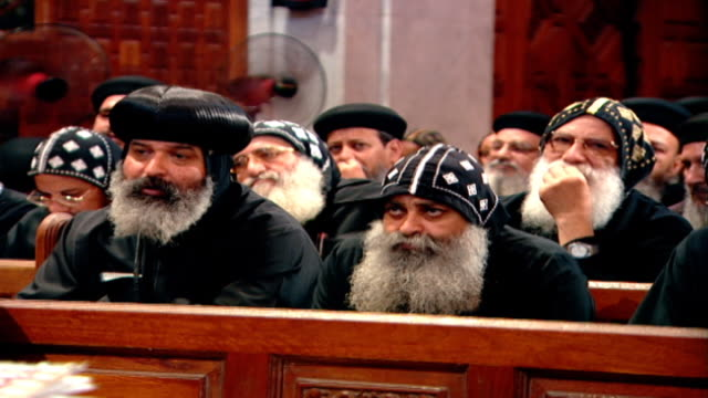 view of coptic monks seated in the pews of st. mark's cathedral in cairo. coptic christians make up 10-15 percent of the egyptian population. - 信者点の映像素材/bロール