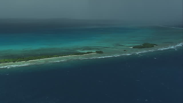WS AERIAL View of coral reefs surrounding isalnd against deep blue ocean and rain pouring in distance / South Africa