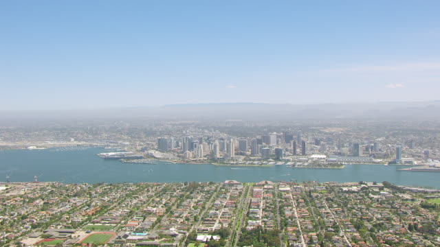 WS AERIAL POV View of Coronado Island in foreground and San Diego Bay with hazy San Diego and Laguna Mountains in background / San Diego, California, United States