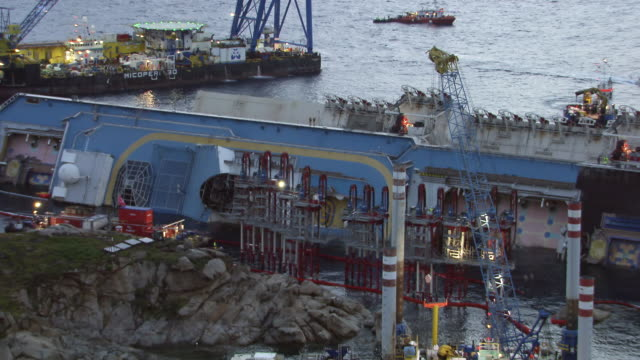 ws view of costa concordia cruise ship lying on its side at dawn surrounded by salvage operation equipment and control barge / giglio porto, tuscany, italy - capsizing stock videos and b-roll footage