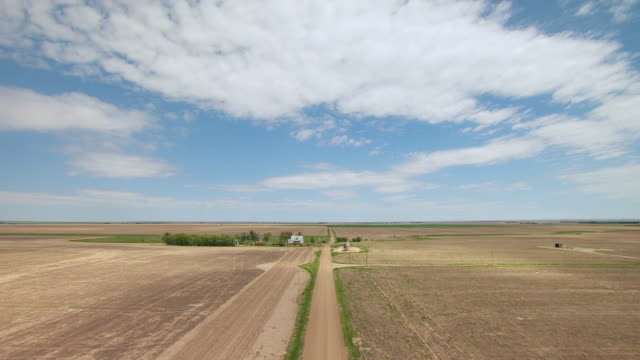 ms aerial view of country road through plains at white farmhouse in gove county / kansas, united states - kansas stock videos and b-roll footage
