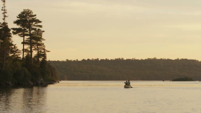 WS TS View of Couple canoeing at sunset on Long Pond / Maine, United States
