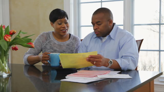 MS View of couple discursing and paying bills at home / Albany, New York, United States