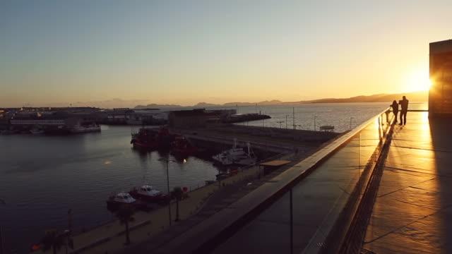 vídeos y material grabado en eventos de stock de ws view of couple enjoying warm sunlight on harbor of vigo - galicia
