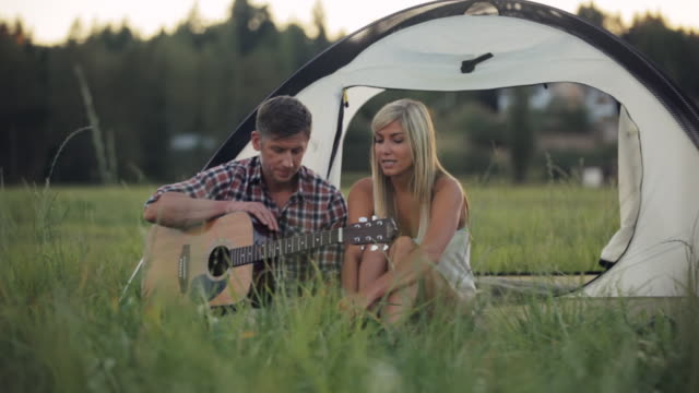 WS PAN View of couple outdoors playing guitar by tent / Langley, British Columbia, Canada