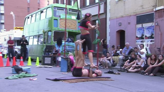 stockvideo's en b-roll-footage met ws zi zo view of couple performing acrobatic tricks on mat at busker fest / toronto, ontario, canada - acrobaat