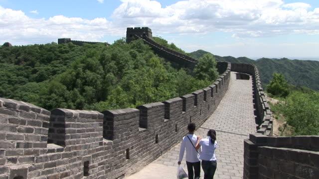 view of couple walking along the great wall of china in beijing china - 万里の長城点の映像素材/bロール