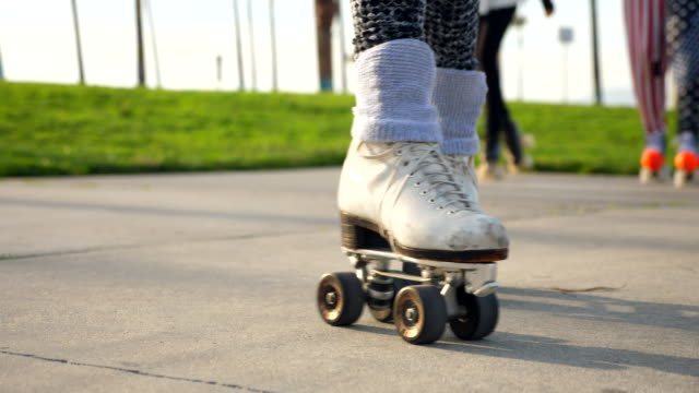 cu view of couples roller skates while they skate together in park - human leg stock videos & royalty-free footage