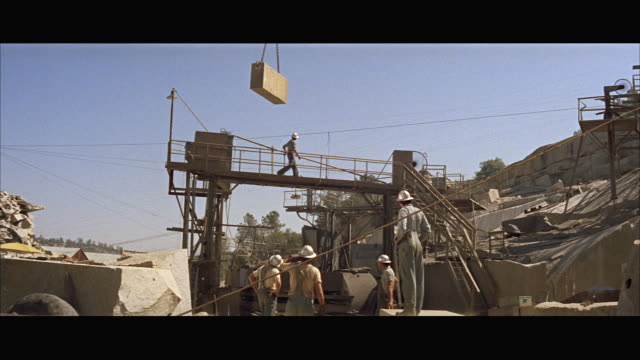 ms view of crane lowering large block of stone - breitwandformat stock-videos und b-roll-filmmaterial