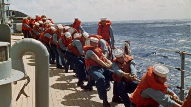 MS CU View of crewmen on navy ships desk