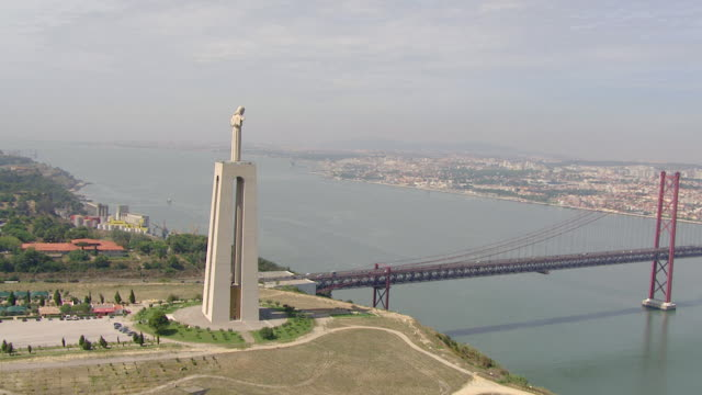 """ws aerial ds view of cristo rei"""" and """"ponte 25 de abril"""" on tagus river / almada, setubal, portugal - statue stock videos and b-roll footage"""