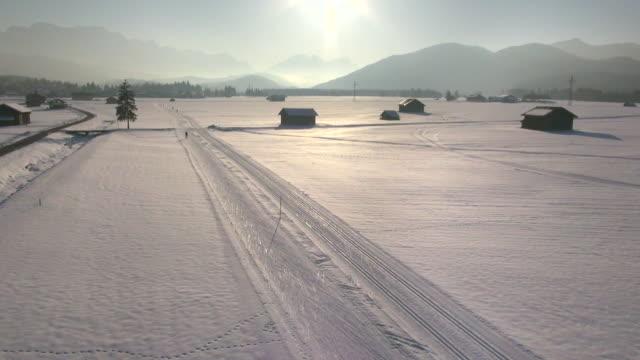 ws aerial view of cross country skier and mountains in winter / wallgau, bavaria, germany - längd bildbanksvideor och videomaterial från bakom kulisserna