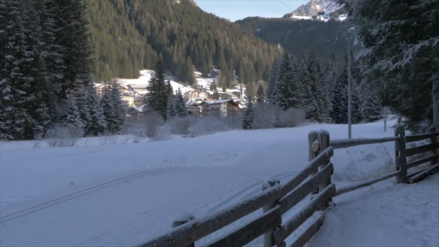 view of cross country skiers near canazei in background, province of trento, trentino-alto adige/sudtirol, italy, europe - canazei video stock e b–roll