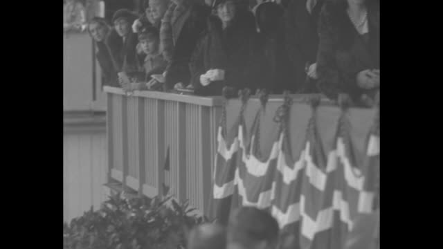 view of crowd at race track / princess ingrid climbs up steps in grandstands to royal viewing box and joins edward and george / horses race in... - steeplechase stock videos and b-roll footage