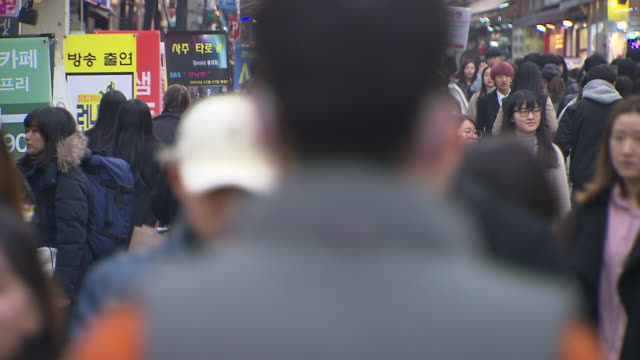 view of crowd walking down the street in hongdae street, seoul, south korea - spending money stock videos & royalty-free footage