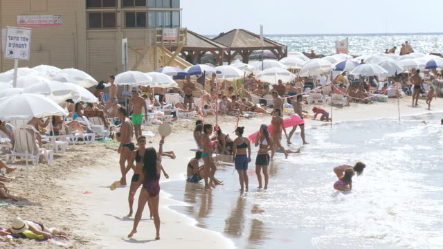 WS View of crowded beach with people with bathing suits having fun on sunny day / Tel Aviv, Dan Metropolitan,Gush Dan, Israel