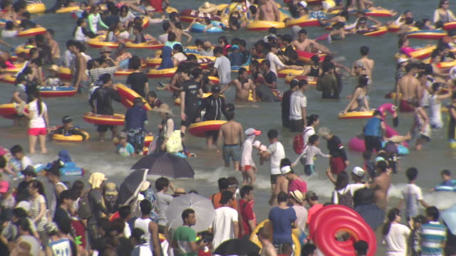 view of crowded tourists swimming in the sea of haeundae beach - rubber ring stock videos & royalty-free footage