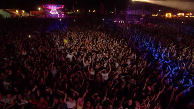 WS POV View of Crowds jumping up and down with spot light searching crowds and purple, blue and red lighting / Victoria Park, London, United Kingdom