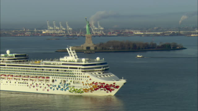 ws zo view of cruise ship 'norwegian gem' passing by statue of liberty at new york harbor / new york city, new york, usa - クルーズ船点の映像素材/bロール