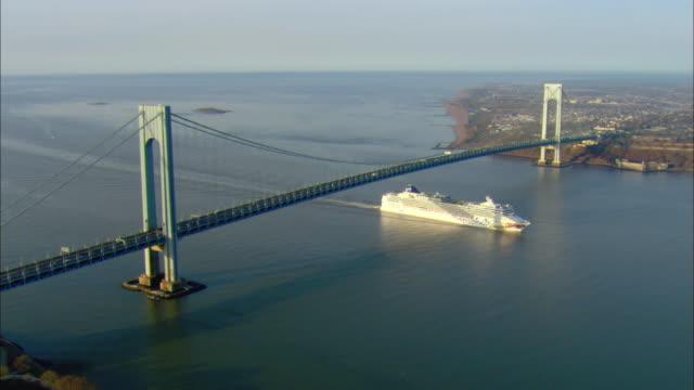 ws pan aerial view of cruise ship 'norwegian gem' passing under the verrazano narrows bridge upon entry to new york harbor / new york city, new york, usa - new yorker hafen stock-videos und b-roll-filmmaterial
