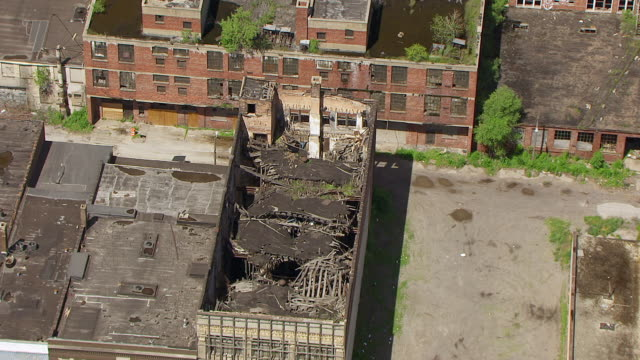 WS AERIAL POV View of crumbling and dilapidated buildings near street / Lake County, Gary, Indiana, United States
