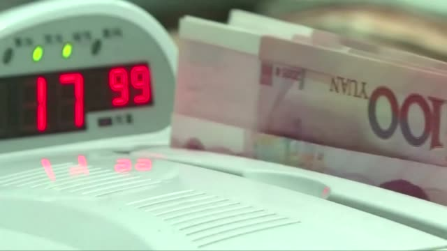 view of currency-counting machine checking a bundle of chinese paper money in south korea - chinese currency stock videos & royalty-free footage