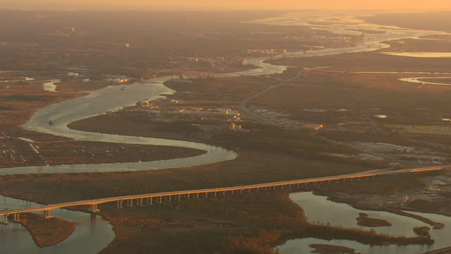 ws aerial view of curve river with wilmington city at sunset / north carolina, united states - wilmington north carolina stock-videos und b-roll-filmmaterial