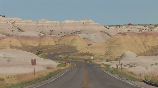 view of curved road in badlands national park united states - badlands national park video stock e b–roll