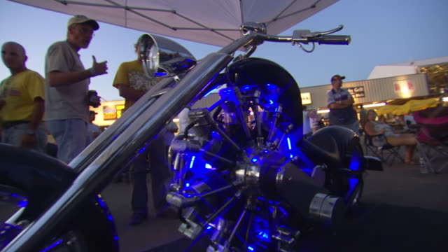 MS POV View of custom motorcycle that glowing neon blue under tent with people looking at it during Sturgis Motorcycle Rally / Sturgis, South Dakota, United States