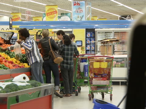 view of customers choosing vegetables from the vegetable stand at a supermarket. - choosing stock videos & royalty-free footage