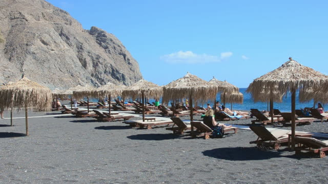 ws view of cyclades perissa famous black sand beaches and straw huts greek relax at beach / santorini, greece - oia santorini stock videos & royalty-free footage